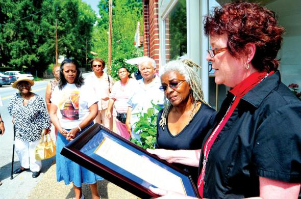 County commissioner Denise Scalph reads the inscription on a plaque at the opening Saturday of the DuBois High School Museum at 116 Main Street in Mount Hope. Looking on is museum curator Jean Evansmore. The location was named a historical landmark.