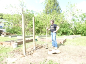 Adam sets posts for Community Garden sign.